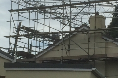 scaffolding on roof of large white home